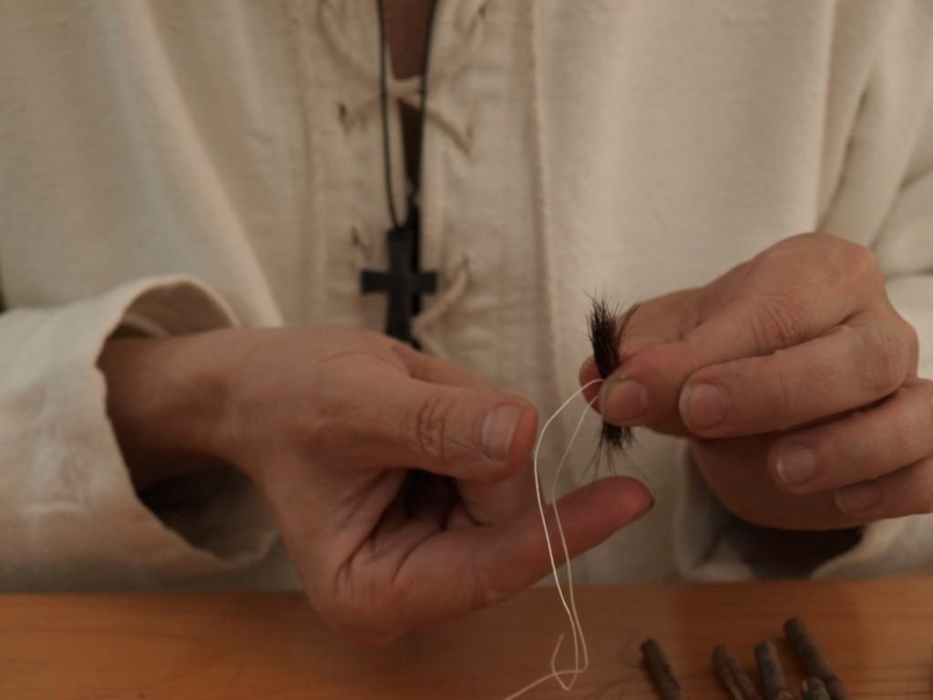 Nouer les poils (ici de la chèvre) avec du fil de lin